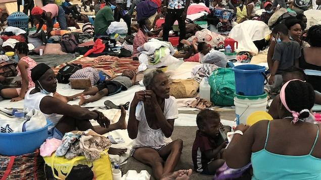 Des dizaines de personnes sont assises sur des matelas posés par terre.