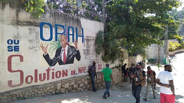 Des Haïtiens marchent devant une murale qui dépeint l'ancien président Jovenel Moïse.