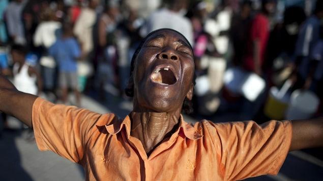 Une femme prie et chante dans une rue de Port-au-Prince, trois jours après le tremblement de terre du 12 janvier 2010.