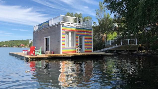 Une petite maison avec terrasse sur le toit se dresse sur un quai flottant près de la berge.