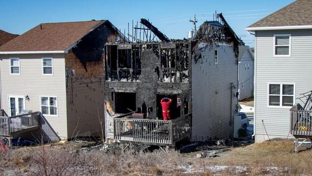 Un pompier examine les ruines de la maison