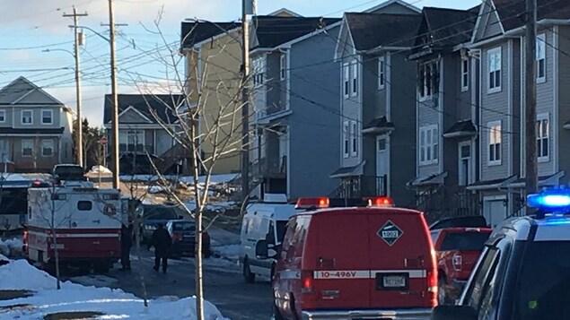 Des véhicules de police et de pompiers devant la maison ravagée par l'incendie