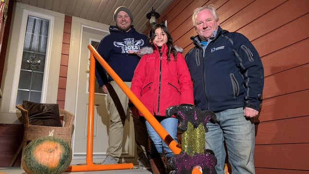 Brandon Lund, Emma Ilagan et George Lund posent à côté de la chute à bonbons.