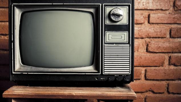 Une ancienne télévision est posée sur un meuble à l'extérieur.
