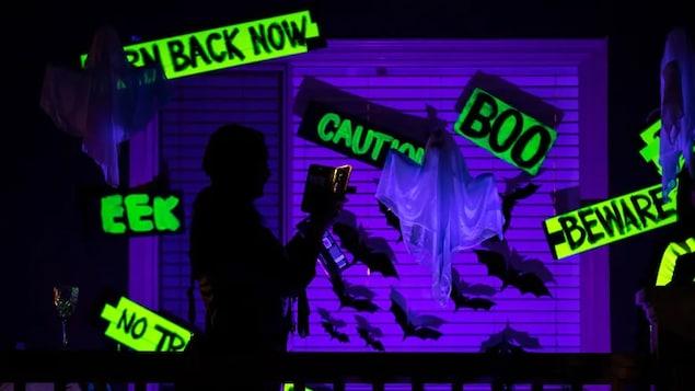 Une personne traverse une salle avec des lumières et des décorations d'Halloween.