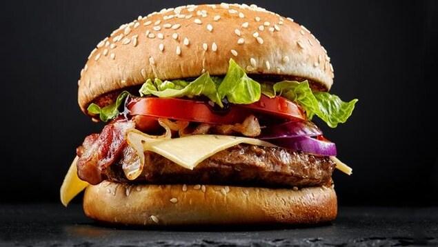 Un hamburger avec de la viande, du fromage, des oignons, du bacon, des tomates et de la salade