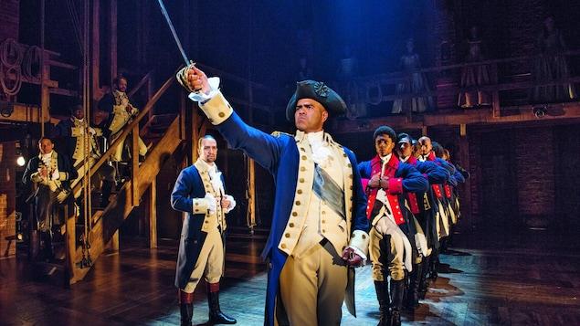 Un homme portant un costume d'époque tient son épée en l'air, tandis que d'autres hommes en costume d'époque l'observent.