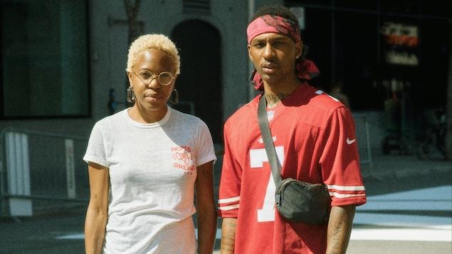Une femme avec des lunettes rondes, et un homme, habillé de rouge, regardent vers la caméra, l'air sérieux.
