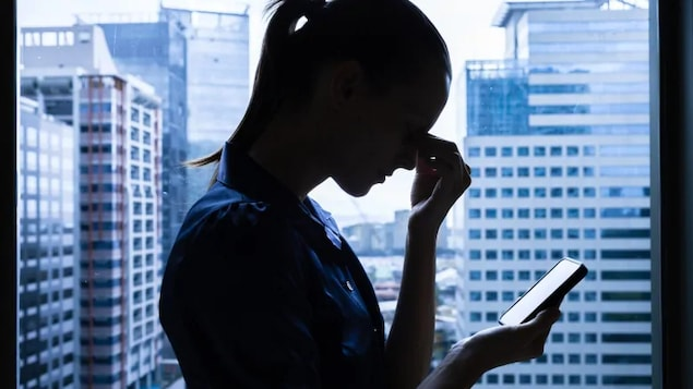 Une femme regarde son téléphone en se pinçant l'espace entre les yeux.