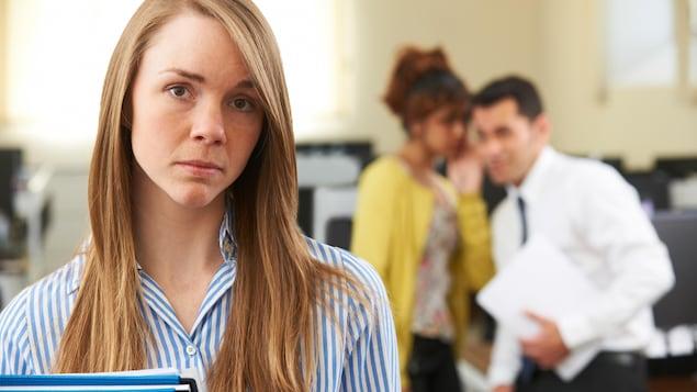 Une femme aux cheveux blonds fixe la caméra des yeux, l'air triste, et l'on peut voir en arrière plan deux de ses collègues, un homme cravaté et une femme portant un blouson jaune, parler entre eux en la regardant.