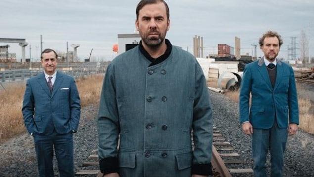 Trois hommes sont debout près d'une voie ferrée et regardent droit devant.