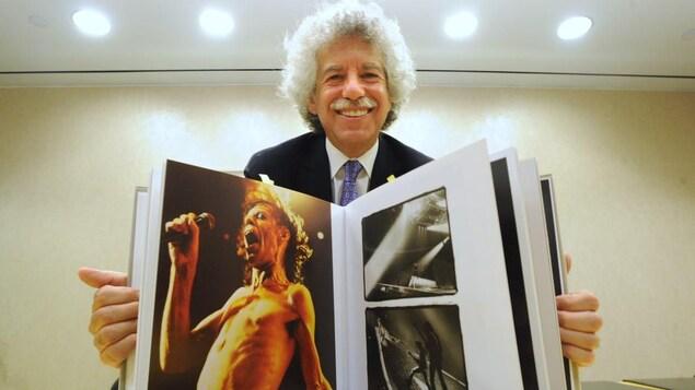 Harley Mintz pose avec un album des photos d'Annie Leibovitz.
