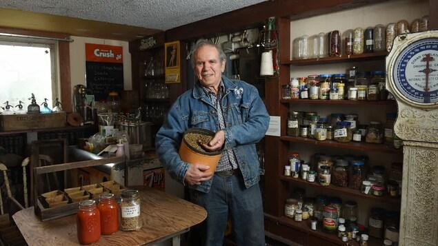Le conseiller municipal Harold Steves est debout à l'intérieur d'un magasin et tient des graines dans sa main.