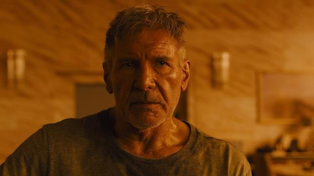 L'acteur Harrison Ford, dans une ambiance ambrée et sombre, dans le film Blade Runner 2049.