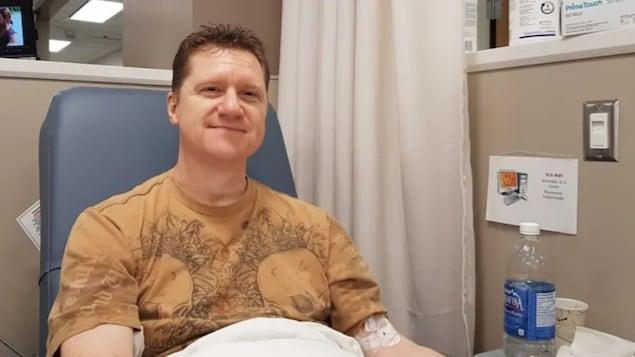 Une photo montrant Thomas Hartle, un homme assis sur une chaise médicale et souriant vers l'objectif