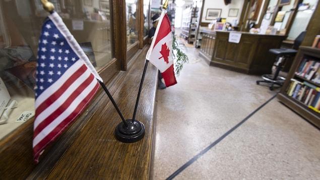 Une ligne marque la frontière entre le Canada et les États-Unis dans la bibliothèque et salle d'opéra Haskell. Des petits drapeaux des deux pays sont disposés sur un bureau dans l'édifice.