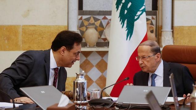 Les deux hommes se penchent l'un vers l'autre en discutant.