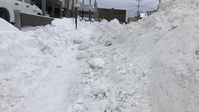 Un trottoir est rempli de blocs de neige.