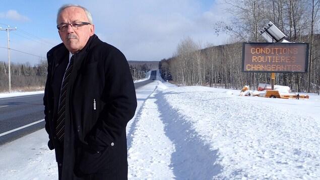M. Flamand se tient en bordure de la route 117, l'hiver, les mains dans les poches de son manteau.