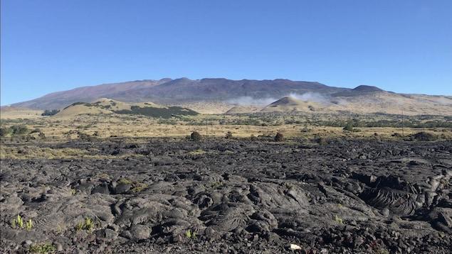 Des roches volcaniques en avant plan, avec une montagne au loin