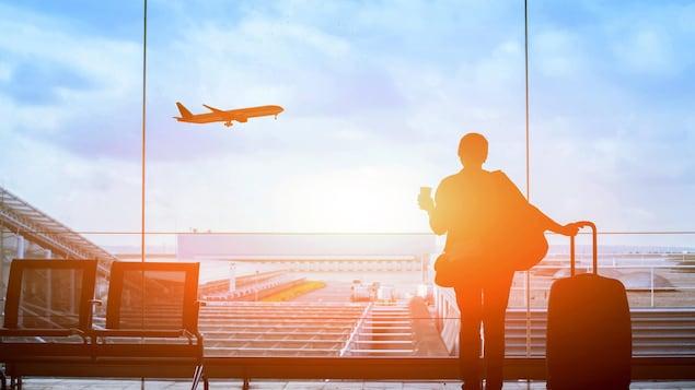 Une femme se tient devant la baie vitrée d'un aéroport pendant qu'un avion décolle sur la piste devant elle.