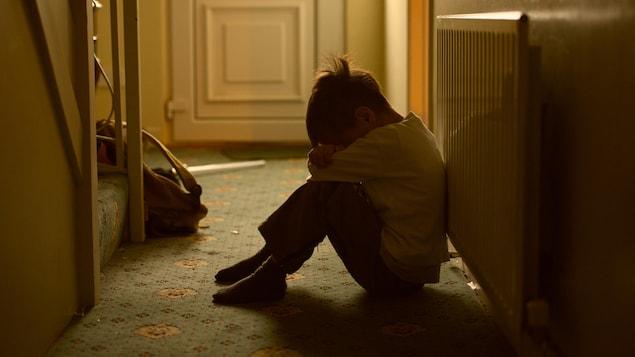Un enfant triste dans l'entrée d'une maison.
