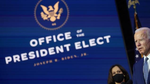 Kamala Harris observe Joe Biden.