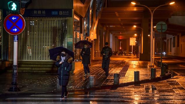 Trois piétons traversent une rue par une nuit pluvieuse.