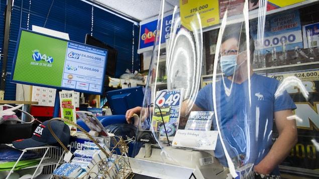 Un employé de dépanneur portant un masque derrière une barrière en plexiglas.
