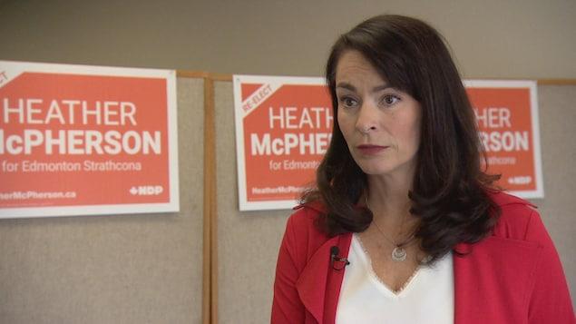 Heather McPherson devant ses affiches de campagne.