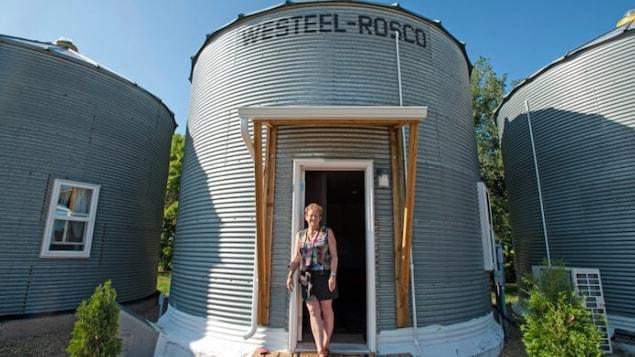 Une dame pose devant un silo à grains qui a été transformé en maison à deux étages.