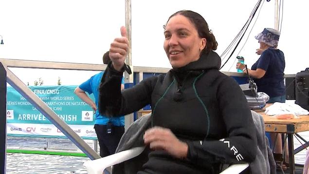 Heidi Levasseur en combinaison thermique à l'extérieur de l'eau, le pouce levé.
