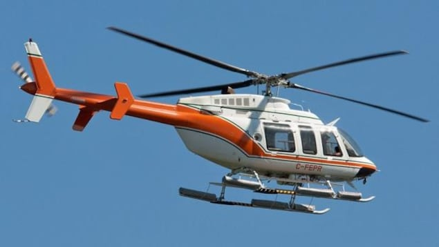 Un hélicoptère Bell 407 est en plein vol.