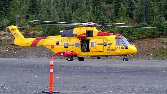 un hélicoptère jaune sur une piste avant un plot orange en premier plan