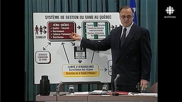 Jean Rochon pointant une grande carte qui illustre les étapes du processus de système de gestion du sang.