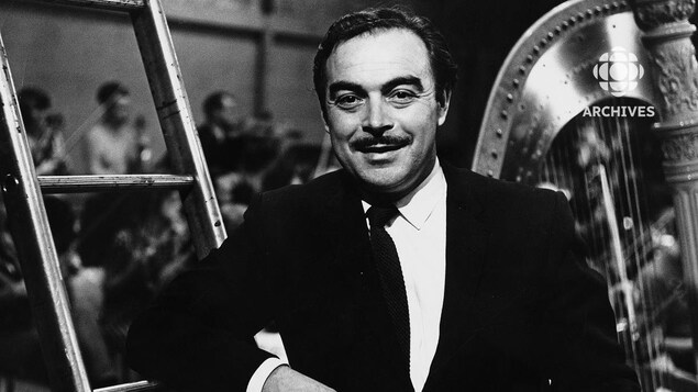 Dans un studio de télévision, Henri Bergeron est debout appuyé à une échelle et derrière lui on voit une harpe. À l'arrière-plan, on voit les musiciens d'un orchestre.