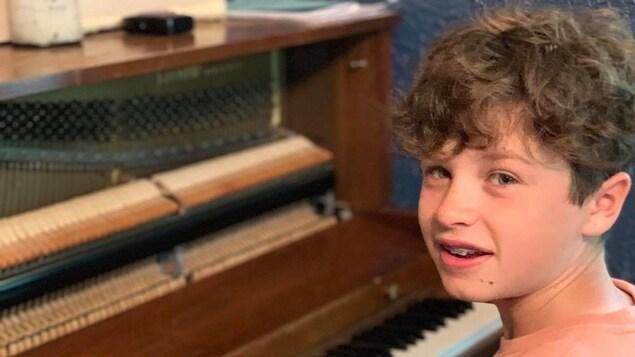Le jeune homme joue du piano.