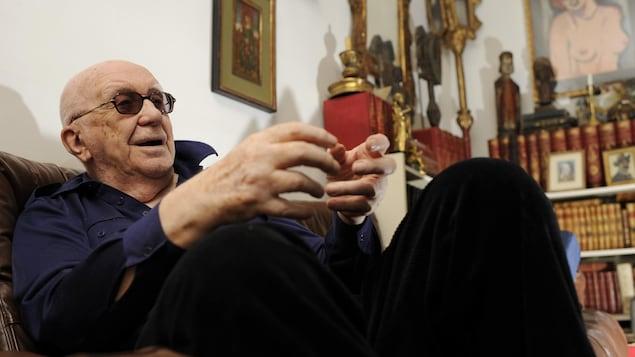 L'auteur est assis sur un sofa dans une pièce meublée par des livres et des peintures.