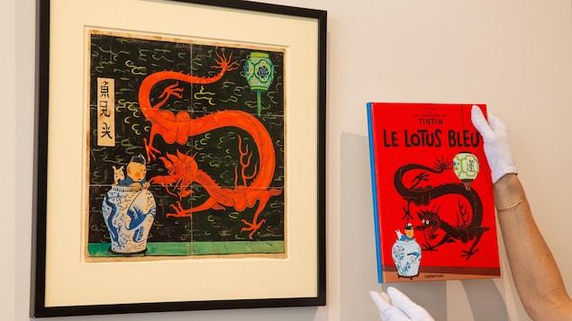 Le dessin où l'on voit Tintin dans un grand vase chinois avec Milou, faisant face à un grand dragon rouge, est encadré et affiché sur un mur. À droite, des mains tiennent une copie de la version imprimée de la couverture du « Lotus bleu ».