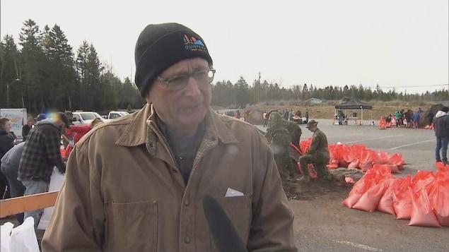 Blaine Higgs en entrevue devant un groupe de bénévoles et de militaires qui remplissent des sacs de sable.