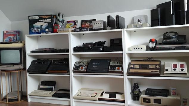 Des étagères où sont placées des dizaines de consoles de jeu vidéo de toutes les époques.