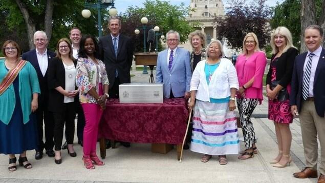 Le premier ministre ainsi que quelques membres du gouvernement et des leaders communautaires debout devant le palais législatif du Manitoba.