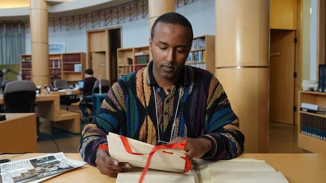 Plan large de Bashir Mohamed assis aux archives provinciales.