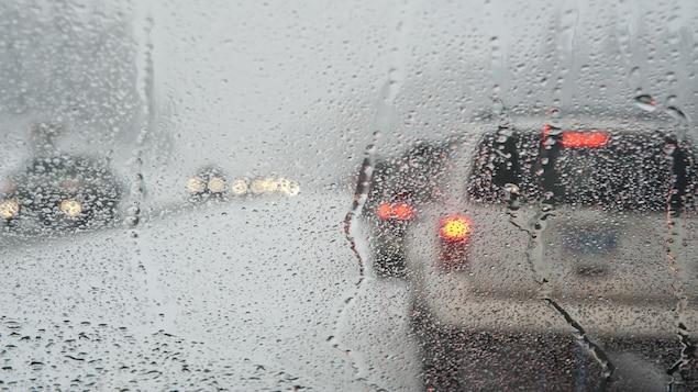 La circulation automobile sur une route sous une pluie abondante.