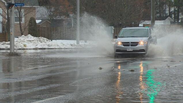 Une voiture circule dans une rue partiellement recouverte d'eau.