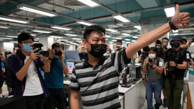 Lam Man-chung, centre, executive editor-in-chief of Apple Daily, gestures June 23 at the headquarters before the newspaper stopped publishing in Hong Kong.
