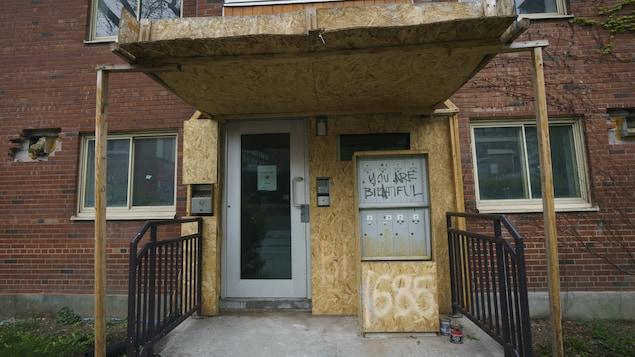 L'entrée d'un immeuble est à moitié barricadée et le mur de brique extérieur compte trois trous.