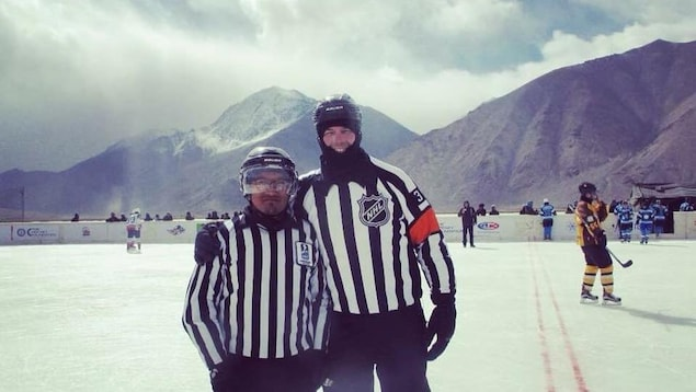 L'arbitre Mike Leggo prend la pause sur la patinoire en altitude avec son adjoint indien.