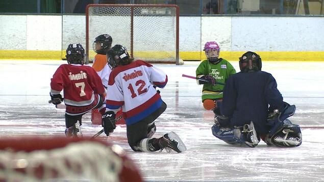 De jeunes joueurs de hockey s'exercent sur une patinoire.