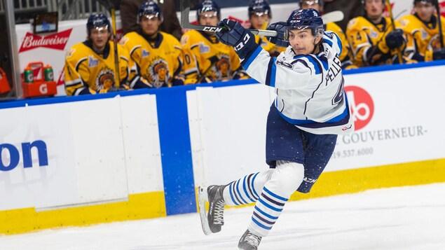 Un joueur de hockey fait un lancer frappé.